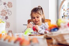 Cute little girl painting egg for Easter royalty free stock image