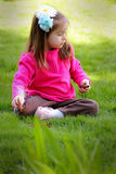 Sweet 2 year old with hair bows. A cute happy little girl in pink with painted fingernails and bows in her long dark hair sitting in the yard playing. Shallow royalty free stock photo