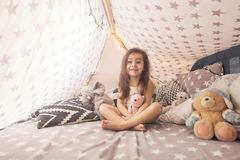 Cute happy little girl playing with toys and dreaming in teepee and bed. Close up photo of happy child.  royalty free stock image