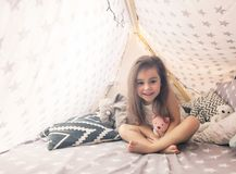 Cute happy little girl playing with toys and dreaming in teepee and bed. Close up photo of happy child stock images