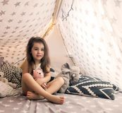 Cute happy little girl playing with toys and dreaming in teepee and bed. Close up photo of happy child stock photos