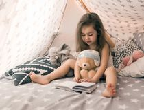 Cute happy little girl playing with toys and reading book in teepee and bed. Close up photo of happy child royalty free stock photography