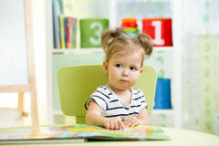 Cute happy little girl reading a book Royalty Free Stock Photo