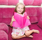 Cute happy little girl reading a book Stock Images