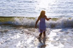 Cute happy little girl running along the beach in jumping over waves. Beautiful summer sunny day, blue sea, picturesque landscape. royalty free stock images