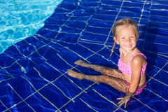 Cute happy little girl in the swimming pool looks Stock Photography