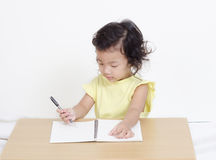 Cute happy little girl writing something Stock Photos