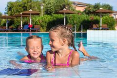 Cute happy little girls having fun in the swimming royalty free stock photography