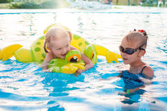 Cute happy little girls having fun in swimming pool Royalty Free Stock Images