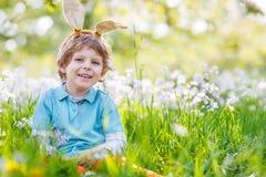 Cute happy little kid wearing Easter bunny ears at spring green. Cute happy kid wearing Easter bunny ears at spring green grass and blooming apple garden Royalty Free Stock Photo