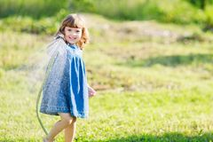 Mothers little helper having fun in the garden. Cute happy little smiling girl watering the garden royalty free stock images