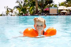 Cute happy little toddler girl swimming in the pool and having fun on family vacations in a hotel resort. Healthy child. Playing in water. Baby in colorful royalty free stock photos