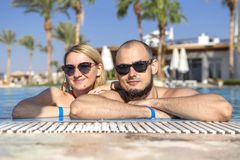 Cute happy loving caucasian couple in a swimming pool in tropical resort outdoors smiling in sunglasses. Lifestyle. Copy space royalty free stock images