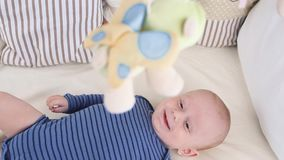 Cute happy 6 month baby boy lying and playing. Little boy looking at his toys stock footage