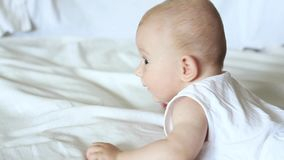 Cute happy 6 month baby boy lying and playing on a white bed stock video