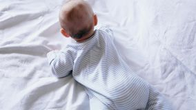 Cute happy 4 month old baby boy lying and playing on a white bed stock video