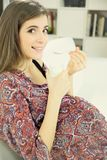 Cute happy pregnant woman eating yogurt sitting on sofa at home. Gorgeous pregnant lady eating yogurt Royalty Free Stock Images