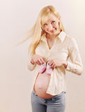 Cute happy pregnant woman expecting a baby girl with little pink Royalty Free Stock Images