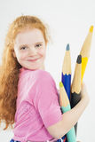 Cute and Happy Red-haired Caucasain Girl Playing with Huge Penci Royalty Free Stock Photography