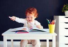 Happy redhead baby boy drawing in developing book at the desk stock image