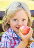 Cute happy school child eating an apple. Cute smiling school child outdoors eating an apple as a healthy snack Stock Photo