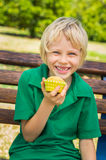 Cute happy school child eating homemade muffin outdoors. Vibrant happy school child eating a homemade muffin outdoors on a park bench royalty free stock photography