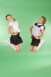Cute happy school girls jumping. Isolated green background. Happiness, friendship, fashionable concept Royalty Free Stock Images