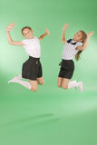 Cute happy school girls jumping. Isolated green background. Happiness, friendship, fashionable concept Royalty Free Stock Photography