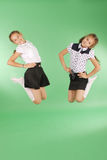 Cute happy school girls jumping. Isolated green background. Happiness, friendship, fashionable concept Stock Photo