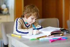 Cute happy schoolkid at home making homework Stock Photography