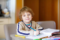 Cute happy schoolkid at home making homework Stock Image