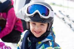 Cute happy skier boy in a winter ski resort Stock Photos