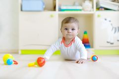 Cute baby girl playing with colorful rattle toys. Cute happy smiling baby playing with colorful rattle toys. New born child, little girl looking at the camera royalty free stock photos
