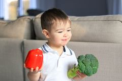 Cute happy smiling little boy holding raw vegetables broccoli and red pepper in his hands. Healthy food, diet, vegetarianism and v royalty free stock images