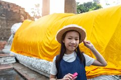 Cute happy smiling tourist girl,Reclining Buddha background. At Wat Yai Chaimngkol, Ayutthaya,Thailand, summer vacation,travel concept stock photos