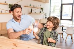 Cute happy son and his father drinking milkshakes. In cafe Royalty Free Stock Image