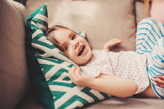 Cute happy toddler girl having fun at home. On the sofa Stock Images