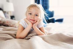 Cute happy toddler girl sitting on bed in pajama. Child playing at home. Casual lifestyle capture Royalty Free Stock Photo