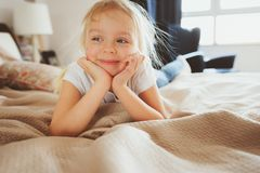 Cute happy toddler girl sitting on bed in pajama Royalty Free Stock Photo