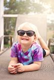 Cute Happy Toddler Girl Smiling as She Lays Outside by the Pool, Wearing Sunglasses. A cute, 2 year old toddler child is smiling as she poses for the camera on a royalty free stock photos