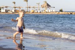 Cute happy toddler on the sea shore. Funny baby boy on vacation Royalty Free Stock Photo