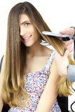 Cute happy woman getting long hair straightened by hairstylist in studio Stock Photo