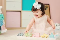 Cute happy 1 year old baby girl playing with wooden toys at home. Royalty Free Stock Photo