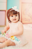 Cute happy 1 year old baby girl playing with wooden toys at home Royalty Free Stock Image