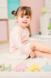 Cute happy 2 years old baby girl playing with toys at home Royalty Free Stock Image