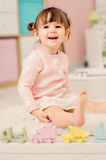 Cute happy 2 years old baby girl playing with toys at home Stock Photography