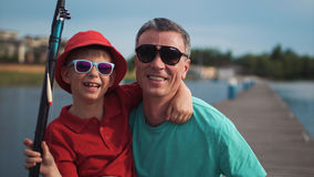 Cute happy young boy with his father at a lake. Cute happy young boy wearing trendy sunglasses posing arm in arm with his father at a lake in front of a jetty Stock Photography