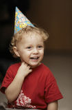 Cute happy young boy in a party hat. Laughing with enjoyment as he celebrates a birthday or Christmas Royalty Free Stock Photography
