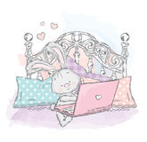 Cute hare in bed with laptop. Bunny the pillows. Royalty Free Stock Photo