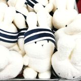 Cute headband bunny soft toys for sale. A photograph showing a big box filled with white soft toy bunnies in navy blue head bands for sale in shopping mall. Cute stock images